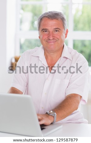 Old man using laptop smiling in kitchen