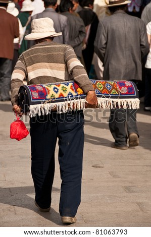 Old man walking with the carpet