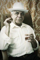 Old man with a cigar and whiskey