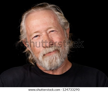Old man with an amused look on his face isolated against a black back ground