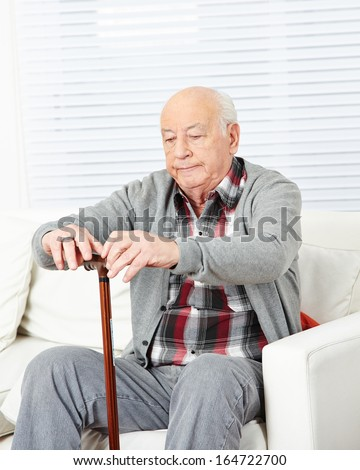 Old man with cane sitting on couch at home