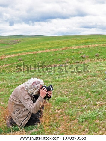 Old man with grey hair taking photo of green spring steppe. Closeup. Selective focus #1070890568