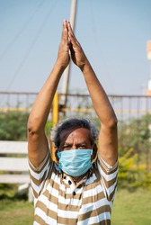 Old man with medical face mask busy doing surya namaskara yoga or exercise during morning - concept of senior people fitness workout and healthcare during coronavirus coivd-19 pandemic.