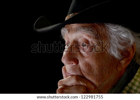 Old man with serious look on face wearing a black cowboy hat isolated on black