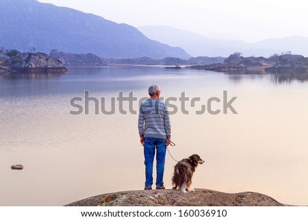 Old man with the dog at the lake in Killarney National Park