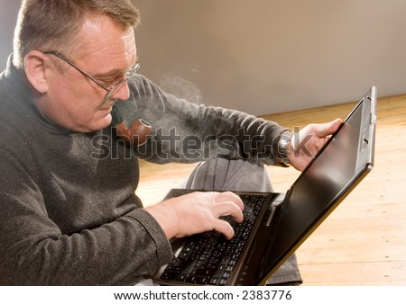 Old man working on the laptop computer smoking pipe stock photo