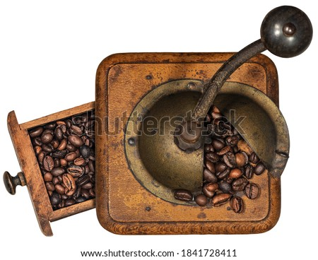 Old manual coffee grinder made of metal and wood with roasted coffee beans isolated on white background. Top view. Italy. Foto stock ©