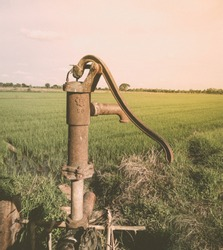 Old manual water pump (Lever pump). Vintage cast iron water pump. (Vintage tone)