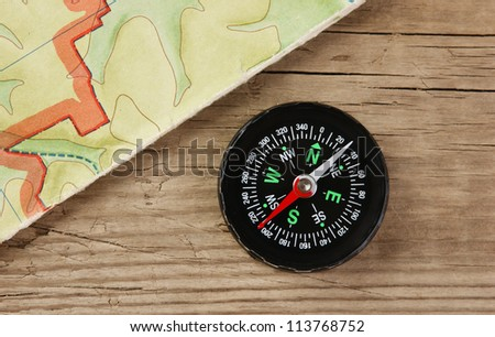 old map and compass on a wooden board