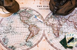 Old map to organize a trip with open borders to leave. Personal accessories such as backpack and hat, money and identity document