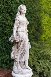 Old marble statue woman with basket of grapes in the park.