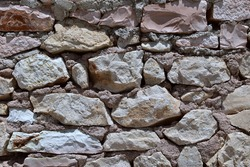 Old masonry of large stones fastened with clay mortar
