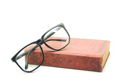 Old math book and  glasses isolated on white