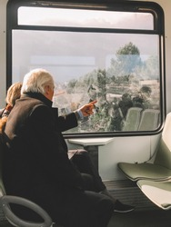 Old mature grey haired couple pensioner travel by train to mountains church Oldman rest on holiday on vacation person aged husband and his wife are in love relax. isolation, quarantine, coronavirus.