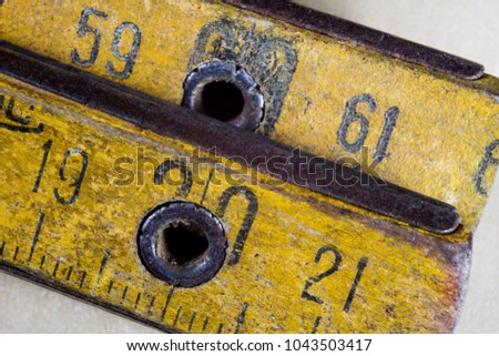 Old measure carpentry on a wooden workshop table. Joinery accessories shown in a large magnification. Light background. #1043503417