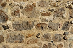 Old medieval castle wall in close up with flints and other stone set in mortar that could be used as a background.