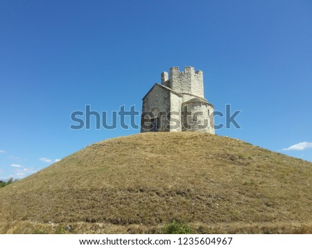Old medieval church with crenelated roof on the artificial mound bellow clear blue summer sky