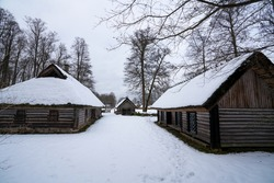 Old medieval log houses. Timber constructions from Estonian history. Peasant homes from the slavery period of Estonian past. Farm yard during winter season. Animals in the sheds. Wood houses