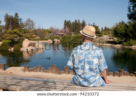 Old men sitting on the bench watching a duck on the lake
