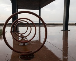 Old metal and brown bicycle stand, bike rack, bike stable, bike stand, cycle stand. Rainy day, sea background.