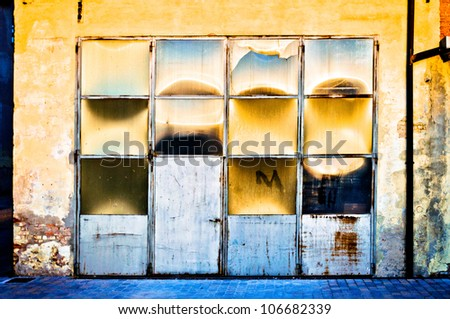 Old metal and glass warehouse door with sun reflections