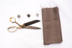 Old metal brass scissors and a fabric with metal bobbins isolated on white background