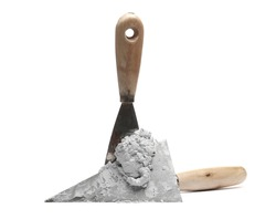 Old metal bricklaying trowel with wet cement, mortar isolated on white background