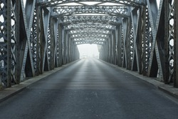 Old metal bridge on a foggy day in Dieppe, France. Empty asphalt road under the metal structure of a city bridge tunnel. Urban scene, city life, transport and traffic concept. Toned