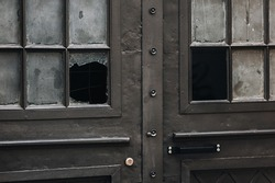 Old metal brown entrance door with broken glass. The concept of burglary, violation of private property rights. Closeup.