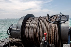 Old metal cable oiled marine winch on the ship on the background of the sea. Steel rope in the sea close-up lubrication. Textural background ship metal cable on a pulley and hired a crane