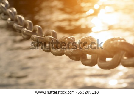 Old metal chain on water background in the sunlight