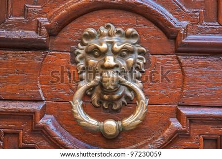 Old metal door handle knocker on a wooden door