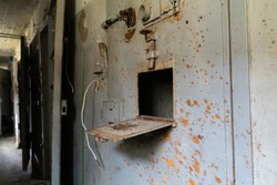 Old metal door of Rummu / Murru prison cells. Small feeding hatch in the middle of the door. Section where the life time prisoners were held. Old soviet style inhumane abandoned prison.