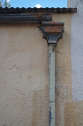 Old metal drainpipe and hopper against the ochre whitewashed wall of an old house.