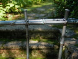 Old metal fence, stylized as bamboo on blurred background of old garden. Bamboo stalks made of metal. The concept of landscape design, stylized as a Japanese garden.Selective focus with Shallow DOF.