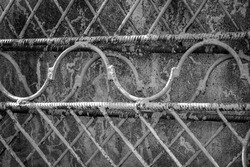 Old metal grating, welded from steel bars and rebar. Paint had cracked and peeled off fence. Against background of concrete wall. Close-up. Selective focus.