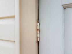 old metal hinge with rust on white door
