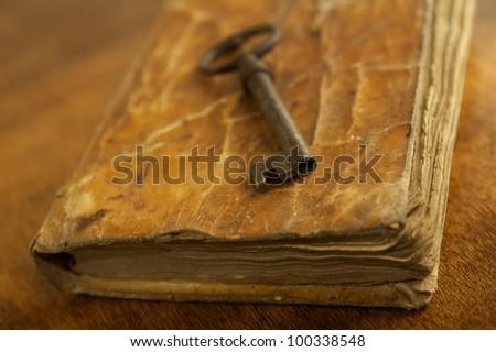 Old metal key on vintage book.