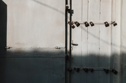Old metal locks on a wooden door with deep shadows from the sun. Many locks on the door.