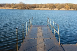old metal pier on the river in autumn