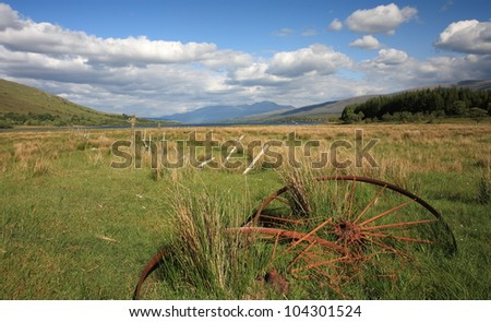 Old metal plough wheels in a long abandoned field with Ben Nevis and Loch Eil in the background.