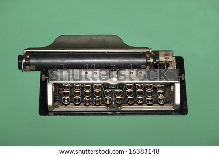 Old metal portable typewriter on a green background.