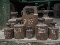 Old, metal weights of different size for a scale