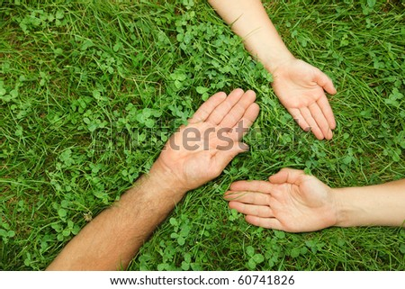 Old, middle aged and young hands in grass, forming a triangle, representing life cycles