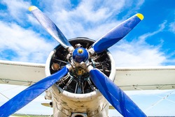 Old military plane propeller closeup. Vintage fighter plane close up by blue sky background