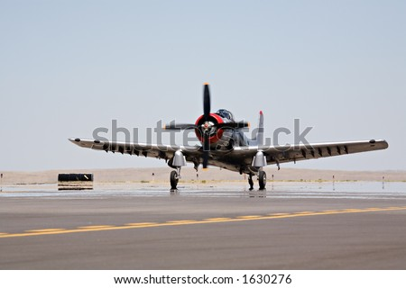 Old military propeller aircraft - a Douglas AD4-NA Skyraider taxiing for takeoff. blue sky with copyspace, motion blur on propeller and focus on canopy.