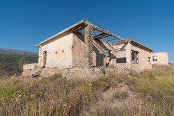 Old mining complex in the south of Spain, the construction is made of stone and brick, there is vegetation and trees, it is a mountainous area, the sky is clear