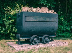 Old mining trolley minecart loaded with stones stands on rails