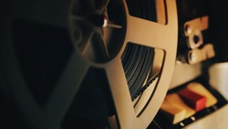 Old 8mm film projector playing in the night. Close-up of a reel with a film.