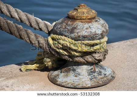Old mooring bollard with heavy ropes a closeup stock for Heavy rope for nautical use